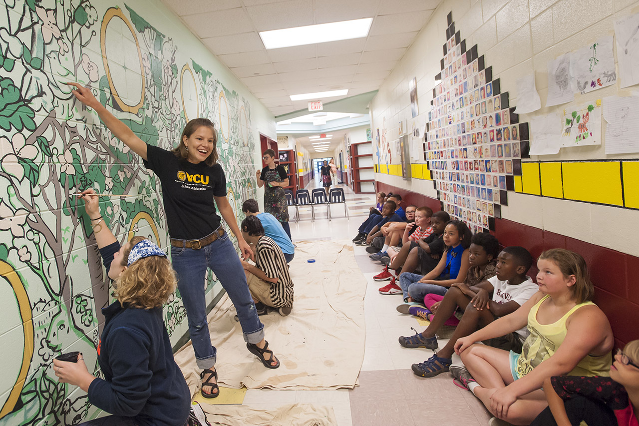 Teachers and students painting mural in school hall
