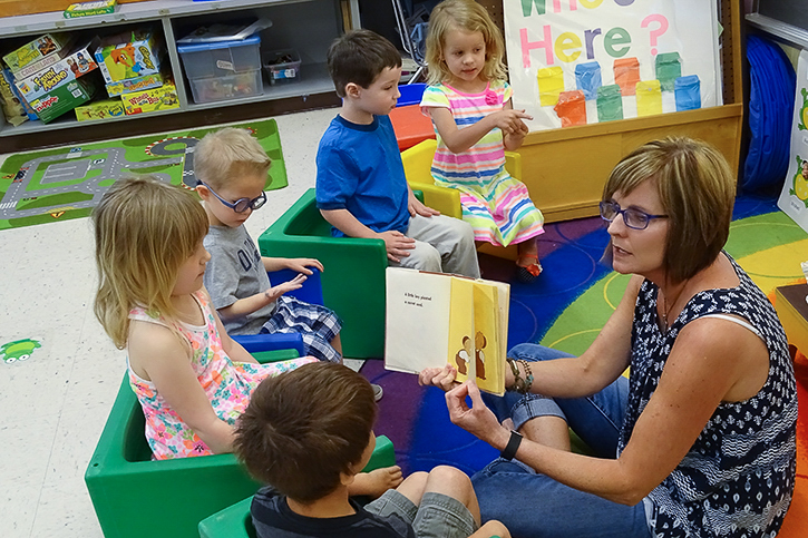 Teacher sitting on the floor reading a book to young children